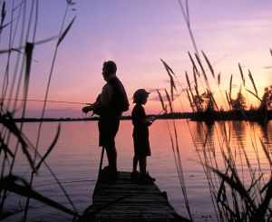 adult and child fishing at sunset