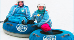 Two kids snow tubing