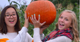 Two girls holding a pumpkin