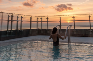 Girl getting out of a pool at sunset