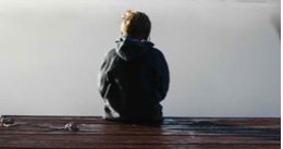 Boy sitting on the edge of a dock