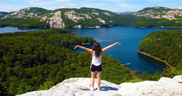 Girl standing at the top of a mountain overlooking a lake