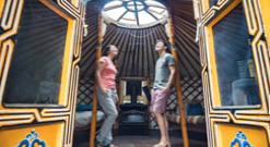 Two people standing in a yurt