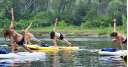 A group of people doing yoga on paddle boards