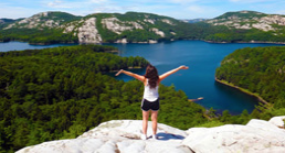 Girl standing onto of a mountain overlooking a lake