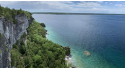 Ariel view of clear blue water and forested cliffs