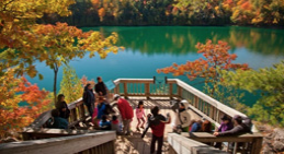 People standing on a deck overlooking a lake and trees